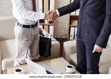 Successful businessmen handshaking after signing contract in office - stock photo