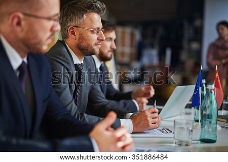 Successful businesspeople listening to speaker at conference or seminar - stock photo