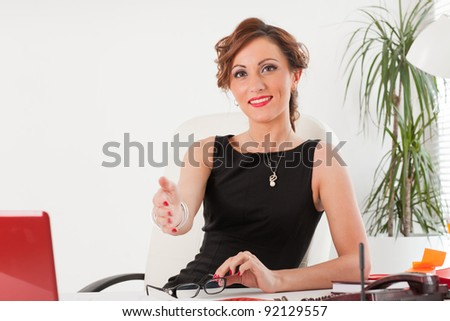 Successful businesswoman at office gives a hand for hand shake.