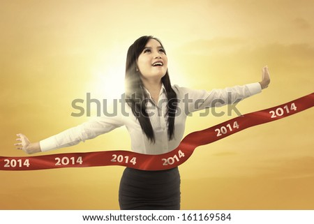 Successful businesswoman crossing the finish line of racing track under sunset - stock photo