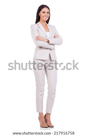 Successful businesswoman. Full length of confident young businesswoman in suit keeping arms crossed and smiling while standing against white background - stock photo