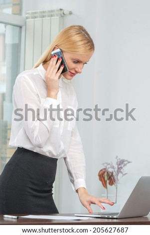 Successful businesswoman or entrepreneur taking notes and talking on cellphone while standing indoor.