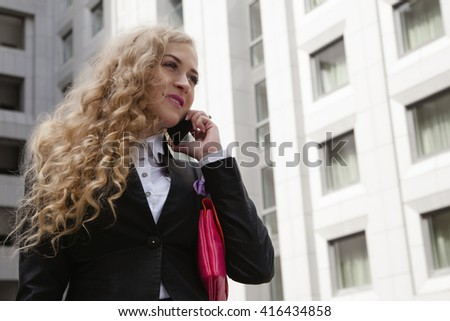 Successful businesswoman or entrepreneur taking notes and talking on cellphone while walking outdoor. City business woman working. - stock photo