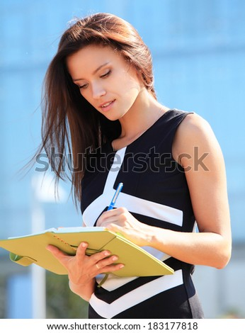 Successful businesswoman or entrepreneur taking notes  while walking outdoor. City business woman working.  - stock photo