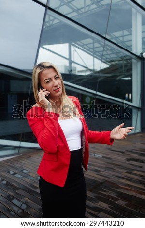 Successful businesswoman or entrepreneur talk on cellphone outdoors, female worker woman dressed in corporate clothing have telephone conversation while standing near office building during work break - stock photo
