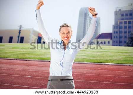 Successful businesswoman raising arms against composite image of racetrack in city - stock photo