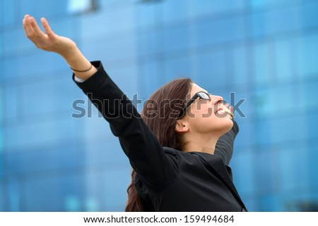 Successful businesswoman raising arms outdoor. Business woman celebrating freedom and success. - stock photo