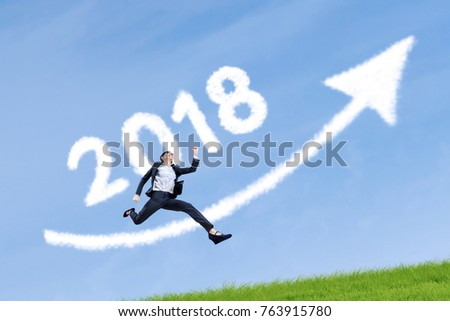 Successful businesswoman running with clouds shaped numbers 2018 and arrow upward in the blue sky