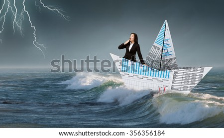 Successful businesswoman sailing on paper boat in financial sea - stock photo