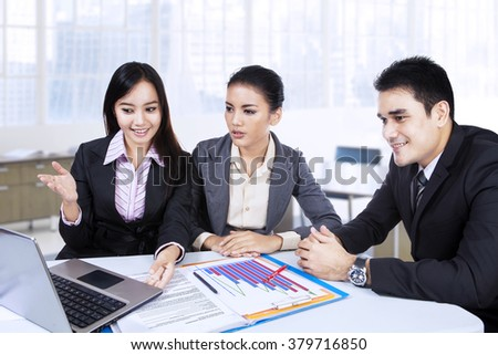 Successful businesswoman showing and explain her idea with laptop computer to her partners in the office - stock photo