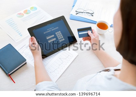 Successful businesswoman sitting at desk in casual clothes and inputting her password and login to carry out online banking operation on digital tablet in the office - stock photo