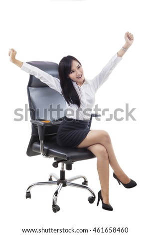 Successful businesswoman sitting on the chair and raising hands up, isolated on white background