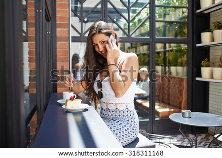 Successful businesswoman talk on smart phone during her work break in modern coffee shop at summer day, seductive young latin female with perfect figure and beautiful breasts having phone conversation