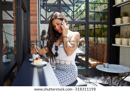 Successful businesswoman talk on smart phone while sitting in cafe terrace during with cup of coffee and cake in the sunny day, seductive female model having cell phone conversation while breakfast