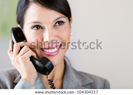 Successful businesswoman talking on the phone and smiling