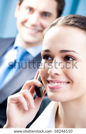 Successful businesswoman with cellphone and colleague, at office - stock photo