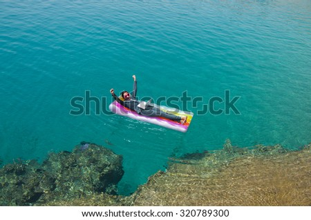Successful  businesswoman with laptop on floating mattress in red sea