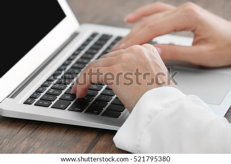 Successful businesswoman working with laptop in office, close up view