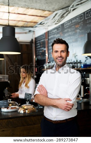 Successful cafe owner standing with crossed arms with employee in background preparing coffee