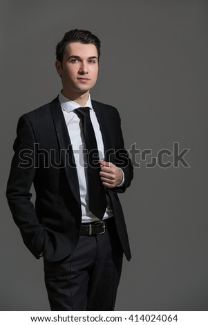Successful caucasian businessman in suit on grey background - stock photo