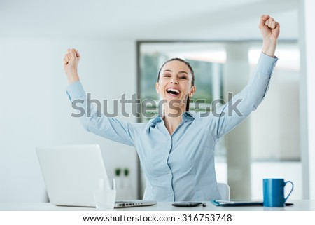 Successful cheerful businesswoman with fists raised sitting at office desk, achievement and satisfaction concept - stock photo