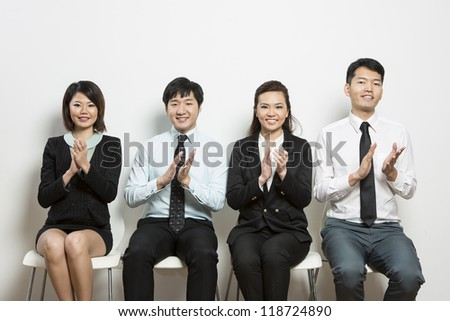 Successful Chinese business team sitting in a row and clapping.
