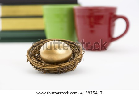 Successful, collaborative investment reflected in two coffee mugs, red and green, and books with selective focus on gold nest egg.  Education, due diligence. and winning strategy in symbols.