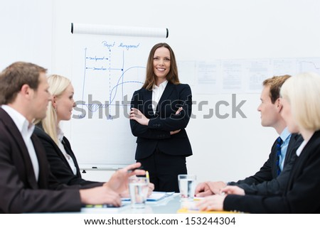 Successful confident young businesswoman giving a presentation standing with folded arms in front of a flipchart facing her colleagues - stock photo