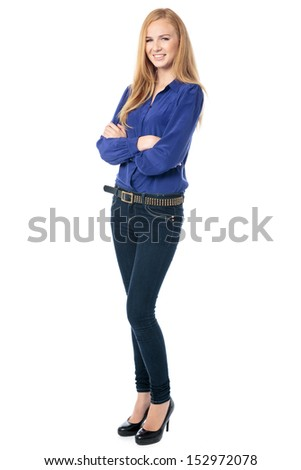 Successful confident young woman with a contented smile standing with her arms folded looking at the camera, full length on white - stock photo