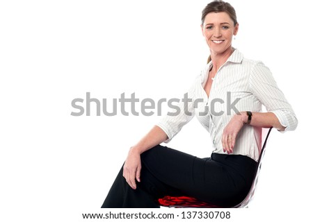 Successful corporate woman sitting on chair with a bright smile on her face. - stock photo