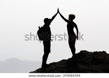 Successful couple achievement climbing or hiking, business concept with man and woman celebrating with arms up raised outstretched outdoors. Motivational and inspirational silhouette landscape. - stock photo