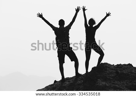 Successful couple achievement climbing or hiking, business concept with man and woman celebrating with arms up raised outstretched outdoors. Motivational and inspirationan silhouette landscape. - stock photo
