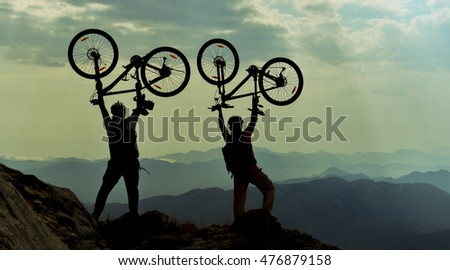 successful cyclists at the peak of the mountain