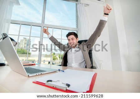 Successful day. Young male businessman enjoys his success and raises his hands while smiling confident businessman sitting in an office at a desk and working on laptop - stock photo
