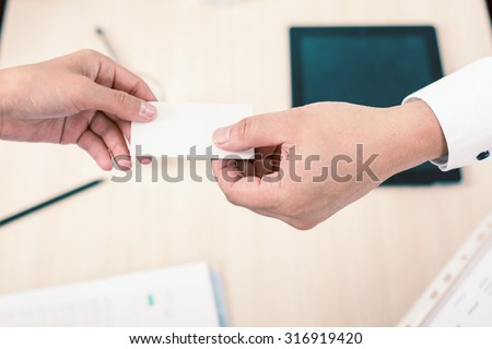 successful deal, businessman gives businesswoman a business card or visit card with a white background on a blank for copy space and any contacts or phone number. Monochromatic color - stock photo