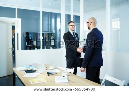 Successful employer shaking hand of new applicant in office