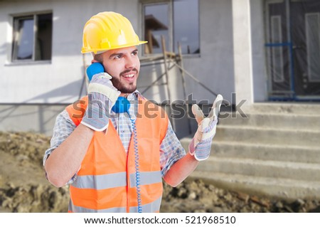 Successful engineer talking business on retro telephone and standing outside in front of renovated house
