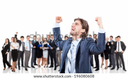 Successful excited business man happy smile hold fist gesture, handsome young businessman with raised hands arms, wear elegant suit and tie over big group of businesspeople human resources background