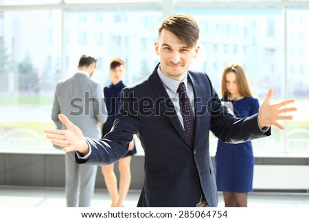 Successful excited businessman looking at camera  with open hands and his coworkers discussing business