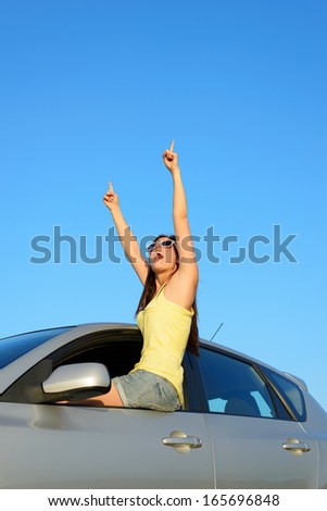 Successful excited woman in new car pointing up for copy space or banner. Young female driver on summer travel. Driving license or vehicle rental concept. - stock photo