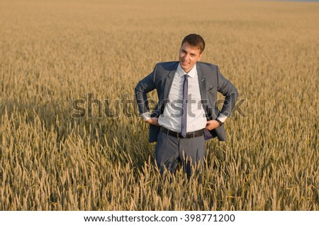 Successful farmer businessman standing in the wheat field  and smiling