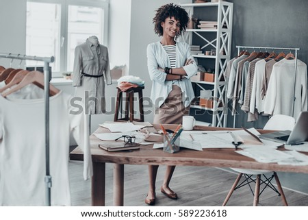 Successful fashion designer. Full length of attractive young African woman keeping arms crossed and looking at camera with smile while standing in workshop