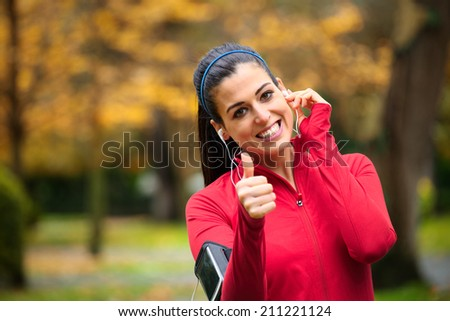 Successful female athlete doing positive thumbs up gesture and wearing earphones before running or exercising outdoor in autumn. Woman success in sport lifestyle. - stock photo