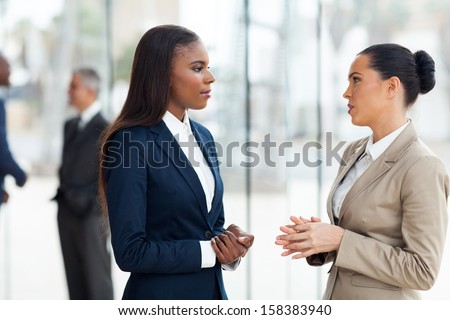 successful female colleagues having conversation in office - stock photo
