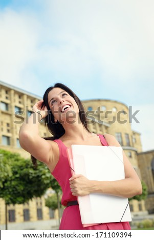 Successful female college student portrait in university campus. Beautiful girl in university looking up. - stock photo