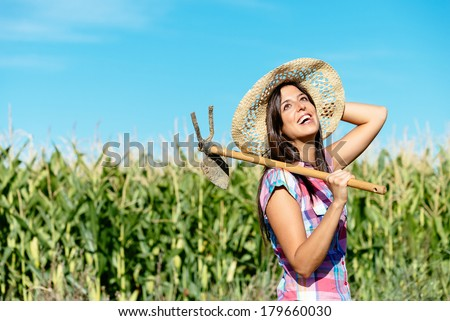 Successful female farmer carrying hoe in corn field and smiling. Countryside woman with work tool wearing straw hat and checkered shirt. - stock photo