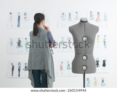 successful female fashion designer looking at drawings in her studio - stock photo
