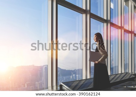 Successful female office worker with net-book is standing in skyscraper interior against big window with city view on background. Proud asian woman architect looking satisfied with completed project - stock photo