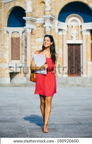 Successful female student at european college. Young woman walking in university campus. - stock photo