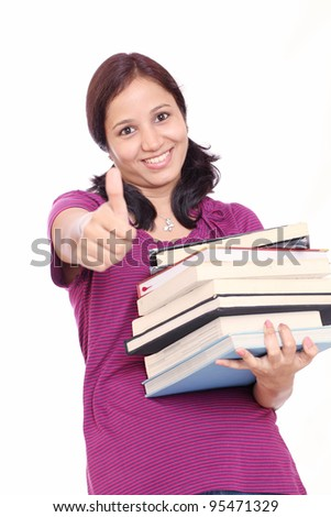Successful female student with her books in hand giving thumb-up gesture